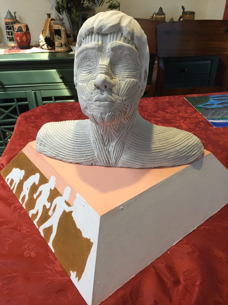 """AVERY CANTRELL From the Inside Out, 2018 Paper clay bust, Wooden base, NFS  Far too often, we take things at face value. This piece is a personal investigation of my own identity, beyond the external. """"From the Inside Out"""" is the literal translation of the ASL sign for transgender, addressing two parts of myself, which I further explored throughout the making of this piece."""